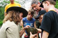 A National Park ranger explains the rock layers to children and families